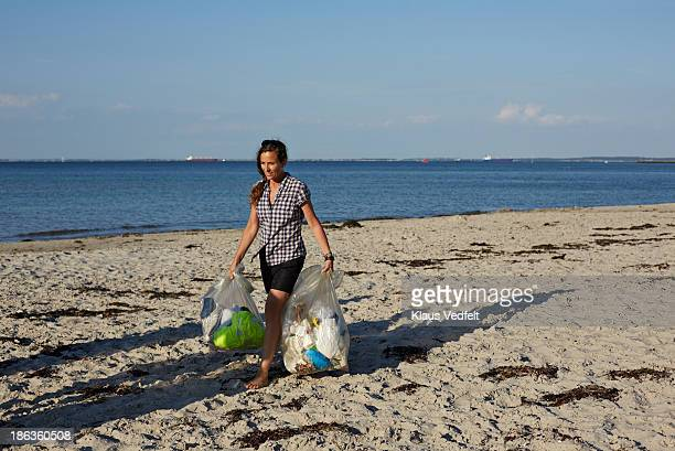 woman carrying trash bags on the beach