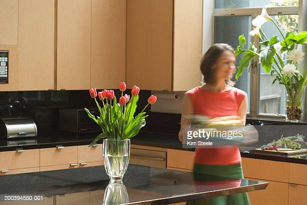Woman carrying tray in modern renovated kitchen, blurred motion