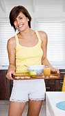 Woman carrying tray of breakfast food