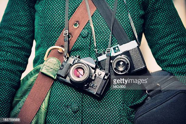 Woman carrying two cameras and bags in a green coat