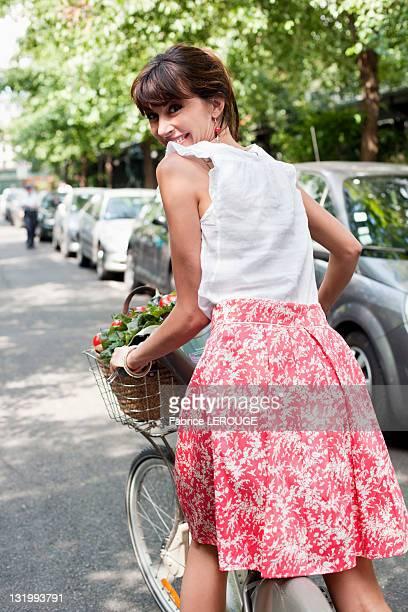 Woman carrying vegetables on a bicycle, Paris, Ile-de-France, France