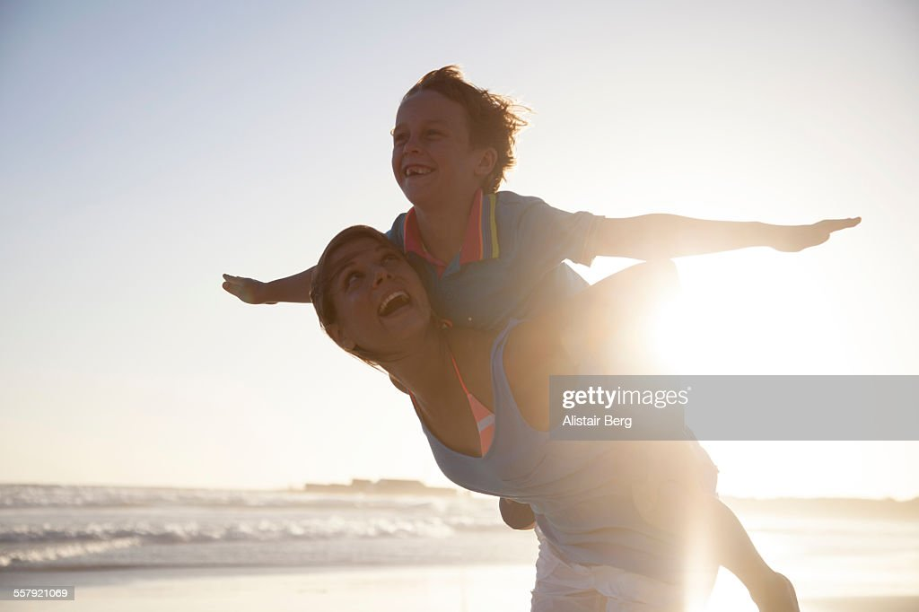 Woman carying boy on beach : Stock Photo