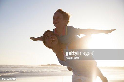 Woman carying boy on beach