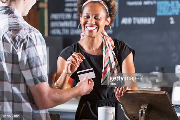 Woman cashier taking payment from customer