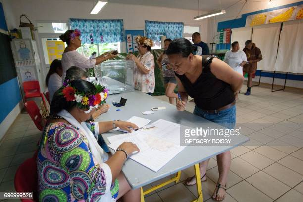 A woman casts a ballot at a polling station during the second round of the French legislative elections on June 17 2017 in Papeete on the French...