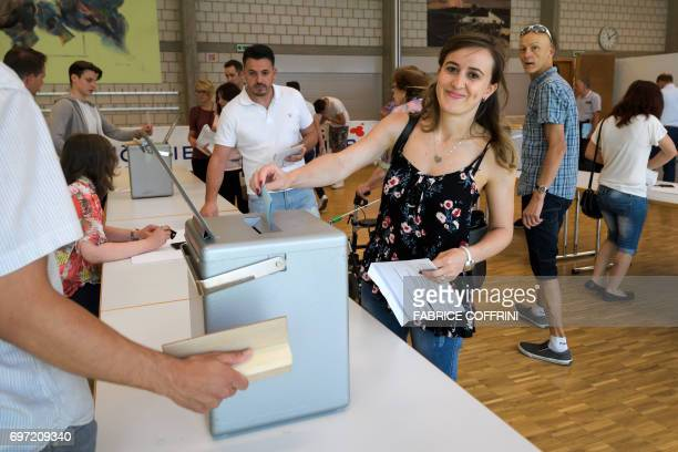 A woman casts a ballot during an election concerning the cantonal membership of the commune of Moutier at a polling station in Moutier northern...