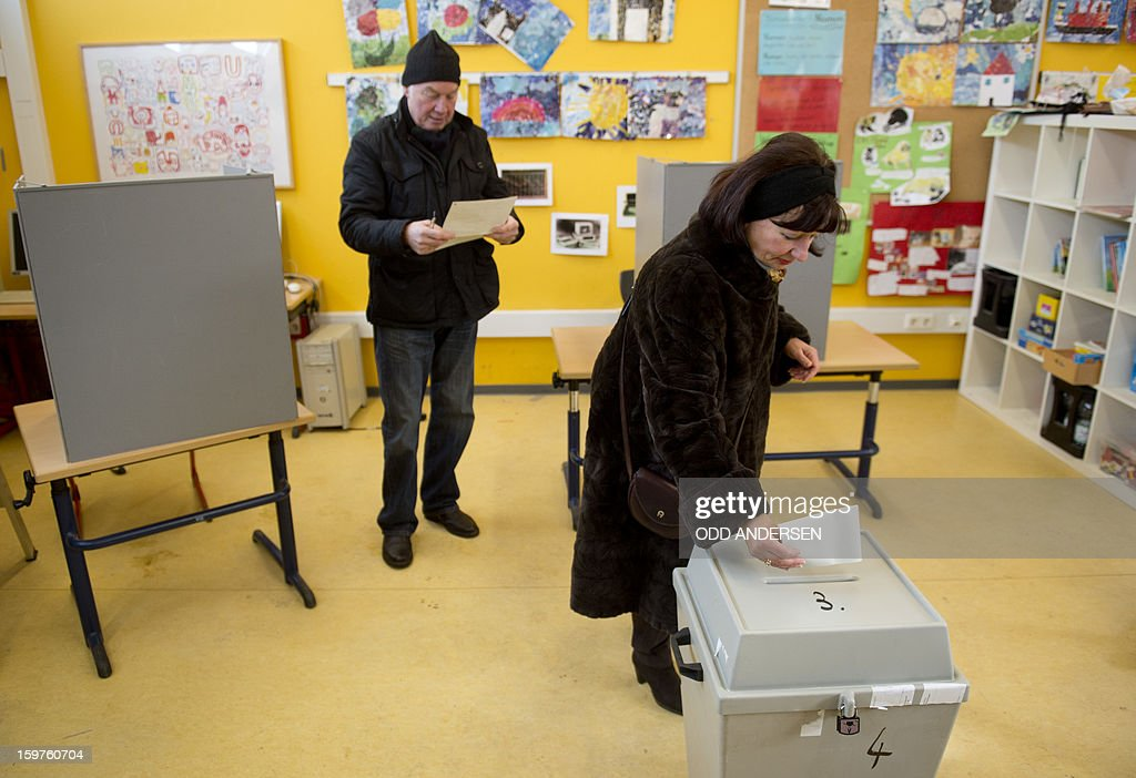 A woman casts her ballot at a polling station at the Friedrich-Dierks Schule in Isernhagen on January 20, 2013 on polling day of the local elections in the central German state of Lower Saxony. The vote is largely seen as a test run for autumn's federal election. AFP PHOTO / ODD ANDERSEN