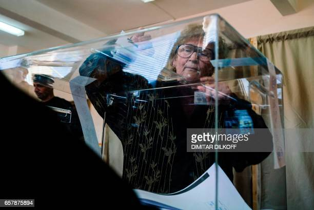 A woman casts her ballot at a polling station in Sofia on March 26 during the country's parliamentary election Bulgaria's election is expected to be...