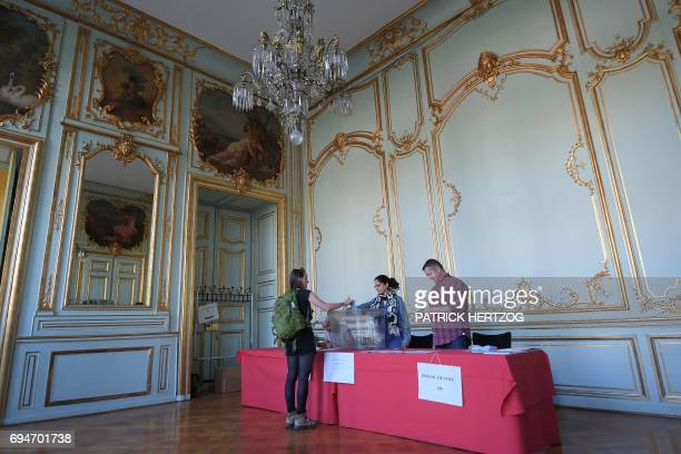 TOPSHOT A woman casts her ballot at a polling station in Strasbourg eastern France during the first round of legislative elections on June 11 2017 /...