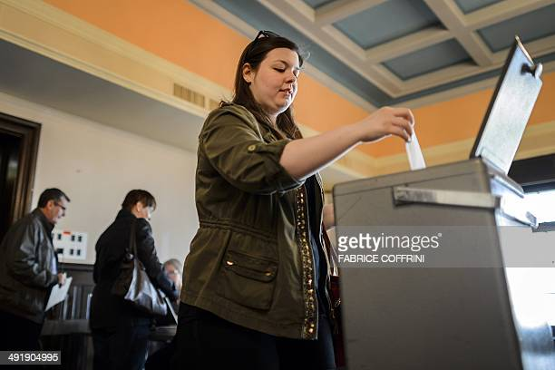A woman casts her ballot during a referendum on May 18 2014 in Bulle western Switzerland Swiss voters are to decide in a referendum on May 18 whether...