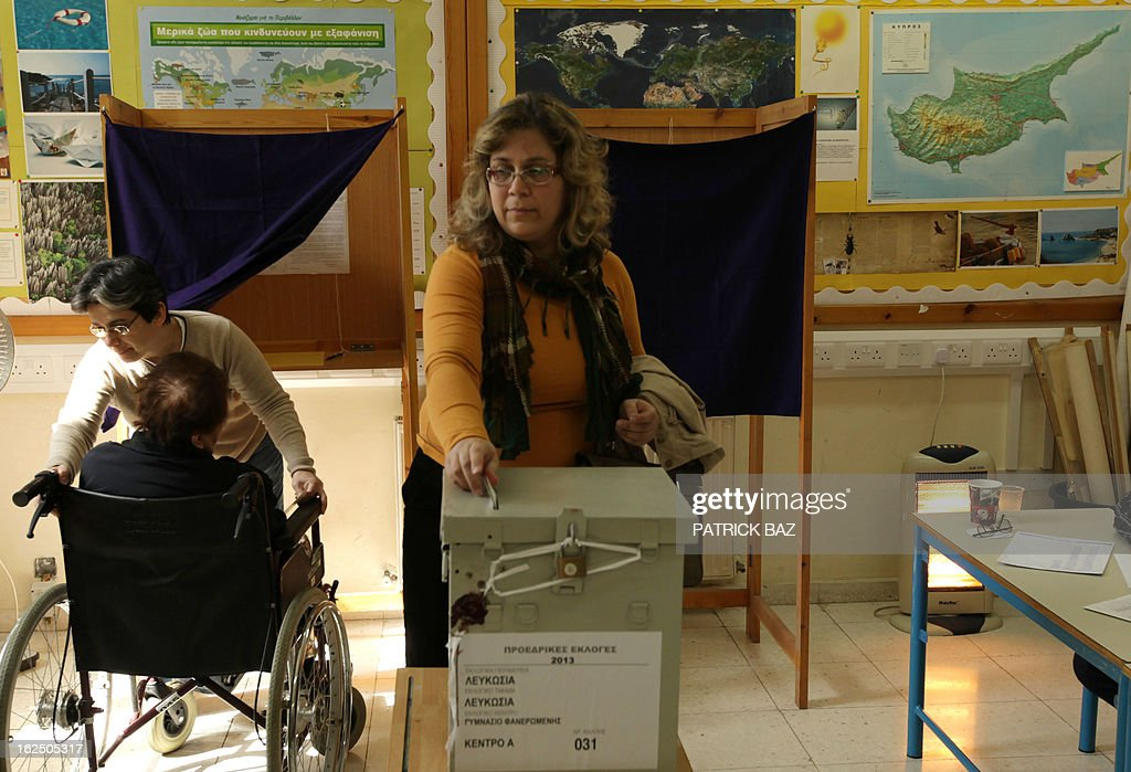 A woman casts her ballot during the second round of Cyprus' presidential election at a polling station on February 24, 2013 in the walled part of the Cypriot capital, Nicosia. Cypriots trickled in under bright, spring-like sunshine to vote in a left-right presidential runoff for electing a new leader to seal a crucial bailout for the EU state on the brink of bankruptcy. AFP PHOTO PATRICK BAZ
