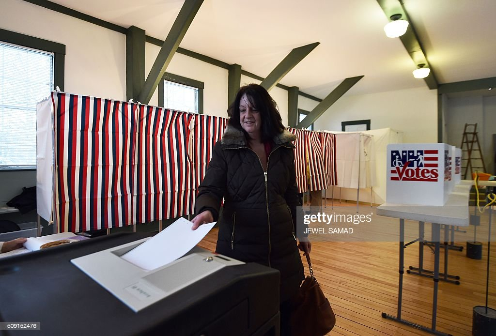 A woman casts her ballot for the first US presidential primary at the town hall in Canterbury, New Hampshire, on February 9, 2016. New Hampshire began voting on February 9 in the first US presidential primary with Republican Donald Trump calling on supporters to propel him to victory and Democrat Bernie Sanders primed to upstage Hillary Clinton. The northeastern state, home to just 1.3 million people, sets the tone for the primaries and could shake out a crowded Republican field of candidates pitting Trump and arch-conservative Senator Ted Cruz against more establishment candidates led by Senator Marco Rubio. / AFP / Jewel Samad