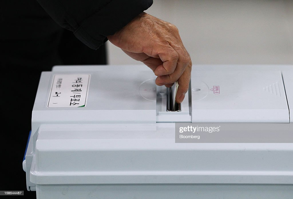A woman casts her ballot for the presidential election at a polling station in Seoul, South Korea, on Wednesday, Dec. 19, 2012. South Koreans go to the polls today to choose either a dictator's daughter or a one-time dissident as president, both of whom pledge to reverse slowing growth, a widening income gap and deteriorating North Korea ties. Photographer: SeongJoon Cho/Bloomberg via Getty Images