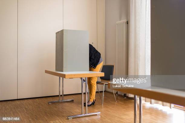 A woman casts her ballot in state elections in North RhineWestphalia on May 14 2017 in Wuerselen Germany The election today the third German state...