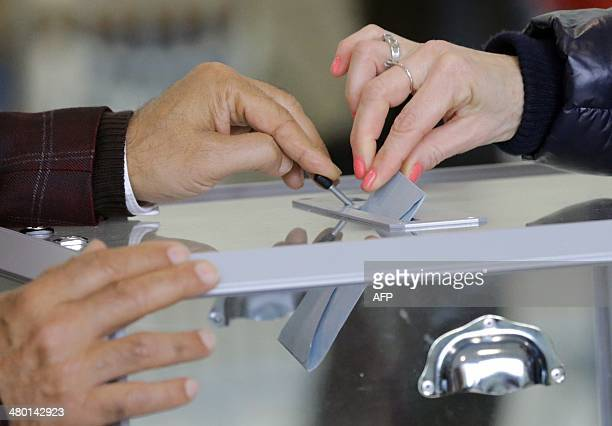 A woman casts her ballot in the first round of the French municipal elections on March 23 2014 at a polling station in VilleneuvesurLot Sunday's...