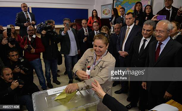 A woman casts her vote as Kemal Kilicdaroglu leader of the main opposition Republican People's Party waits to cast his vote at a polling station...