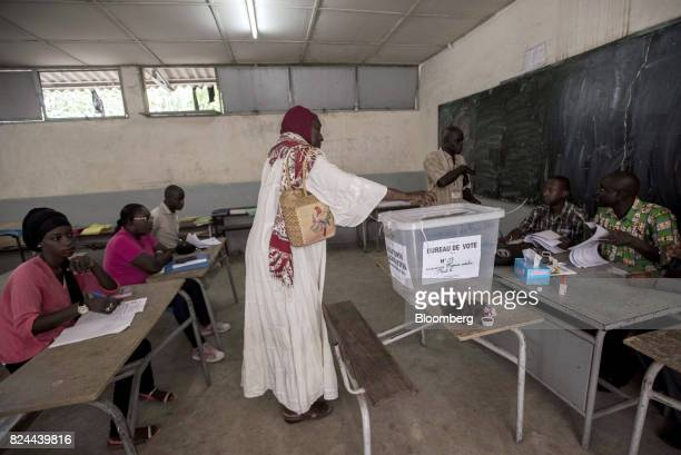 A woman casts her vote in a ballot box at a polling station during parliamentary elections in Dakar Senegal on Sunday July 30 2017 Senegalese voters...