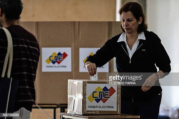 A woman casts her vote in a polling station in Caracas on December 6 2015 during the Venezuela's legislative elections For the first time in 16 years...
