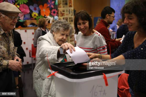 A woman casts her vote into the ballot box at a polling station as voting continues in the referendum on October 1 2017 in Barcelona Spain More than...