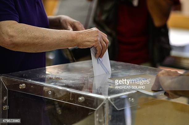 A woman casts his ballot at a polling station during the Greek referendum in Athens on July 5 2015 Greek voters headed to the polls to vote in a...