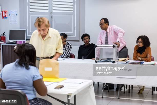 A woman casts his ballot during the second round of the French legislative elections at the polling station number 1 in Cayenne on June 17 2017 / AFP...