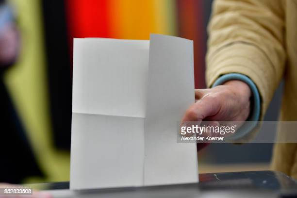 A woman casts in her election ballots at a polling station during German federal elections on September 24 2017 in Berlin Germany German Chancellor...