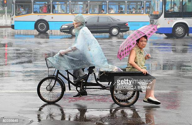 A woman catches a ride on the back of a tricyle during a morning rainfall in Beijing on August 10 2008 Beijing will remain hazy hot and humid with a...