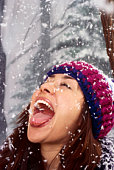 Woman catching snowflakes in her mouth