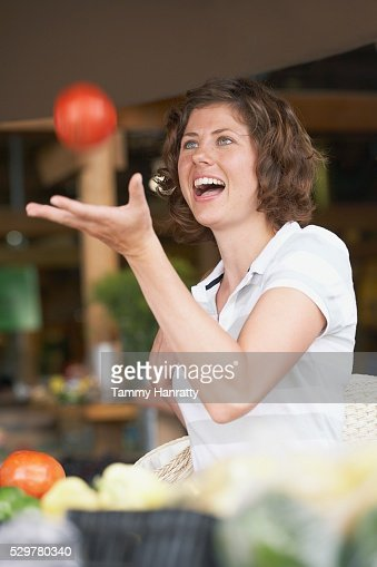 Woman catching tomato : Bildbanksbilder