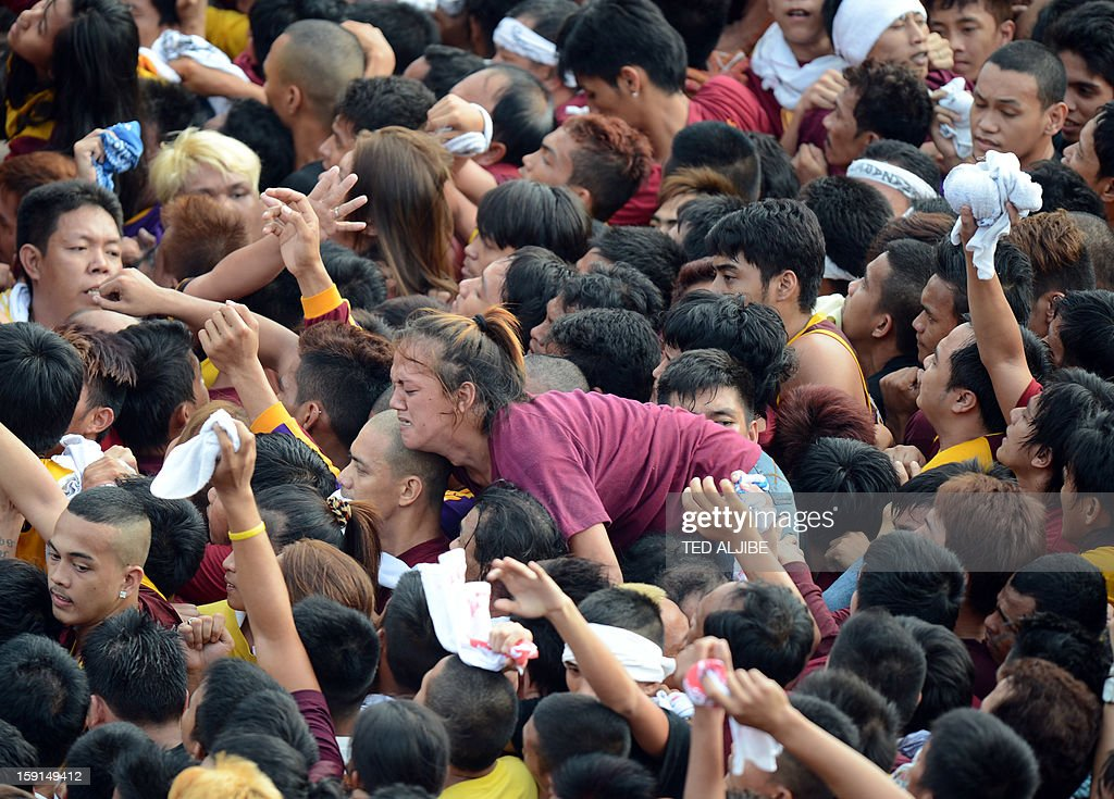 A woman Catholic devotee jostles for position as she tries to reach the statue of the Black Nazarene (not pictured) during the annual procession in honor of the centuries-old icon of Jesus Christ, in Manila on January 9, 2013. Masses of Catholic devotees swept through the Philippine capital on January 9, in a spectacular outpouring of passion for a centuries-old icon of Jesus Christ that many believe can perform miracles. AFP PHOTO/TED ALJIBE