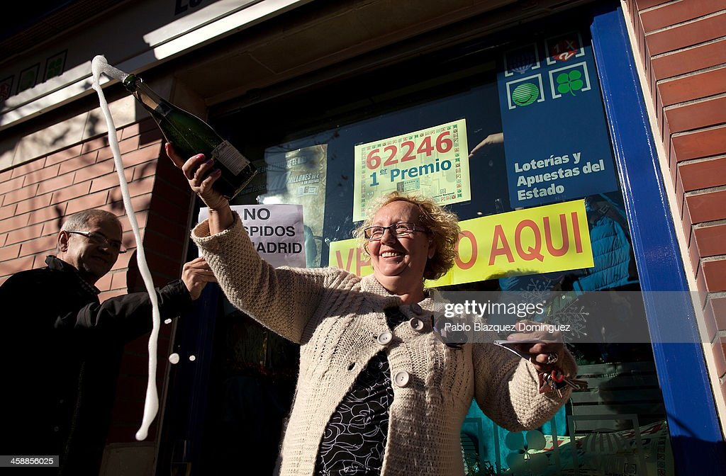 A woman celebrates next to the local lottery administration which sold the first prize tickets in Spain's Christmas lottery, 'El Gordo' (Fat One) on December 22, 2013 in Leganes, near Madrid, Spain. This year's winning number is 62246, with a total of 4 million euros for the top prize to be shared between ten ticket holders. The total prize fund is worth 2.5bn.