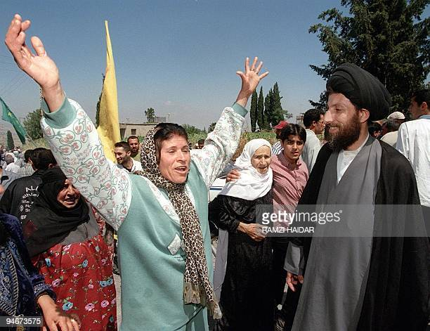 A woman celebrates with Hezbollah cleric Sayed Hassan Nasrallah in the southern Lebanese village of Marqaba 22 May 2000 after Israel's proxy South...