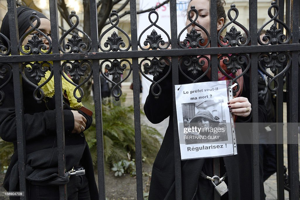 A woman (R) chains herself to the gate of the Socialist party (PS) headquarters on January 3, 2013 in Paris, during a protest of people who chained themselves to the gate of the PS headquarters as they call for the regularization of immigrants in the French northern city of Lille. Protestors claimed to act in support of Lille's fifty people who have begun a hunger strike since early November. Placard reads: 'Does the prefect want me to die? Give regularisation!'.