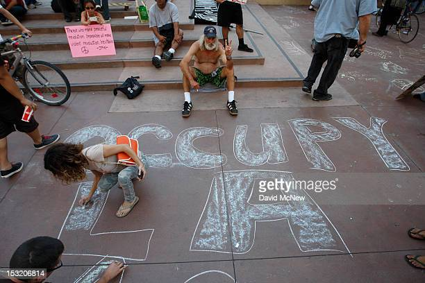 A woman chalks a message on the sidewalk as protesters rally in the downtown financial district to mark the oneyear anniversary of the Occupy...