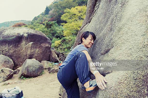 Woman challenging rock climbing