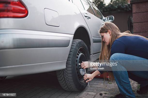 Woman changing a car tire.
