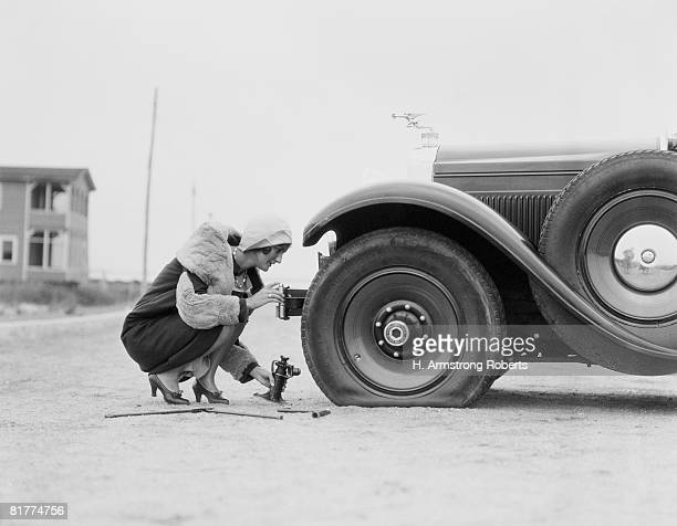 Woman changing flat tire on car.