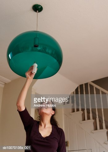 Woman changing lightbulb at home : Stock Photo