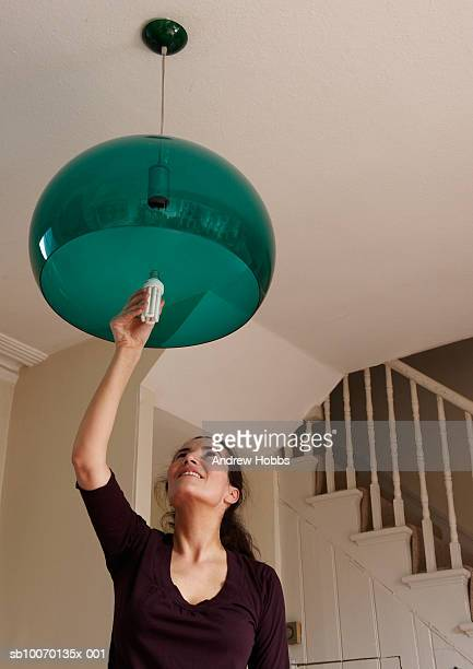 Woman changing lightbulb at home