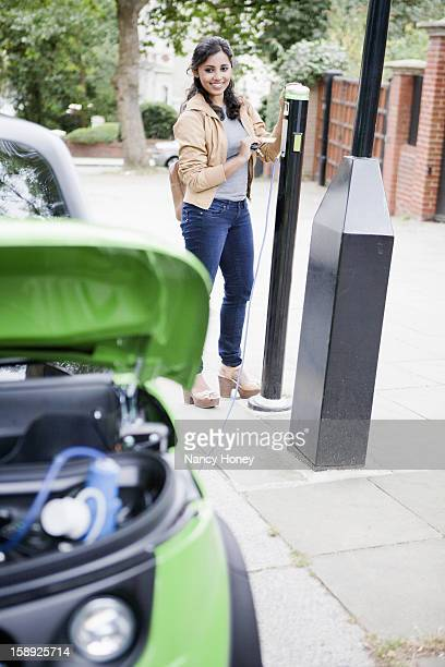 Woman charging electric car on street