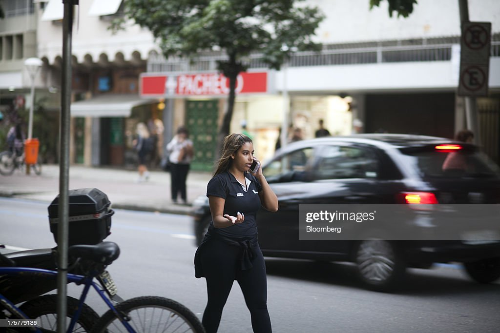 A woman chats on her mobile phone in the Ipanema neighborhood of Rio de Janeiro, Brazil, on Tuesday, Aug. 6, 2013. Telefonica Brasil SAs Vivo, now controlling 28.7 percent of Brazil's mmobile phone market is locked in a battle with Tim Participacoes SA, whose share of the market has risen to 27.2 percent by undercutting rivals on voice and data plans. Photographer: Lianne Milton/Bloomberg via Getty Images