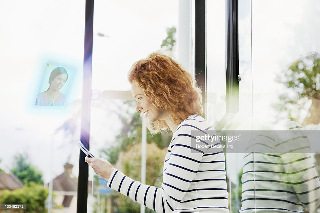 Woman chatting to friend on smart phone : Stock Photo