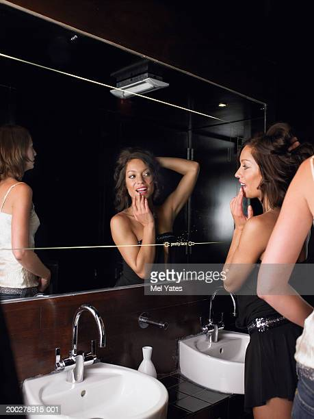 Woman checking appearance in mirror in club toilets, smiling