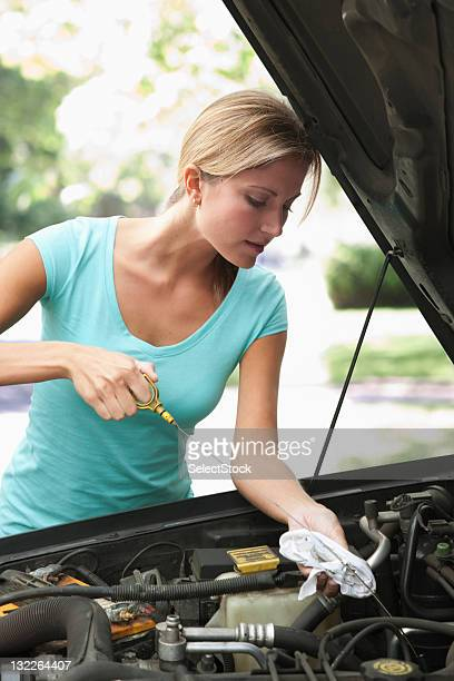 Woman checking car oil