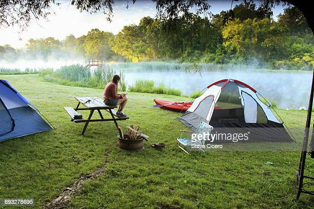 woman checking cellphone at campsite