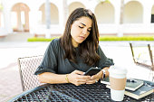 Mid adult woman checking email box on smartphone at table in garden