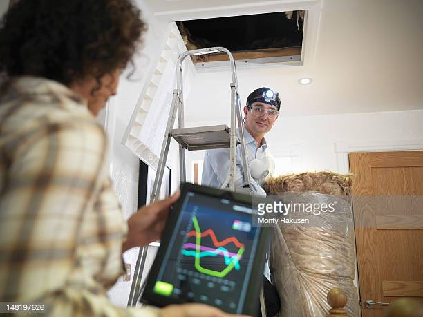 Woman checking energy usage on digital tablet as man prepares to insulate loft