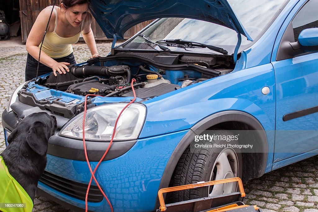 Woman checking engine of broken car : Stock Photo