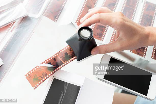 Woman checking film strips with magnifying glass