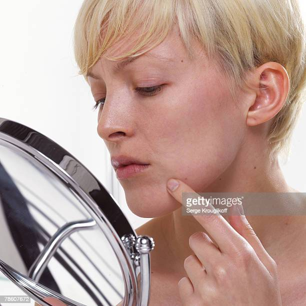 Woman checking for acne in vanity mirror